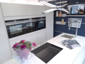 Pronorm Y Line In Magnolia Gloss. Illuminati Wave (double Pendant Light) in the Alex Lee Kitchens, Rugby Showroom.